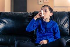 Muchacho que sostiene el inhalador del asma imagen de archivo libre de regalías
