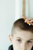 Muchacho que sostiene el lápiz en su cabeza para comprobar altura Foto de archivo libre de regalías