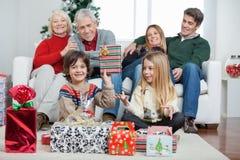 Muchacho que sostiene el regalo de la Navidad con la familia en casa Fotos de archivo libres de regalías