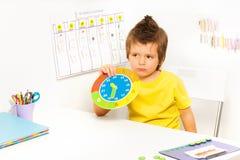Muchacho que sostiene el reloj del cartón que se sienta en la tabla Imagen de archivo libre de regalías