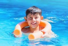 Muchacho que sostiene encendido la boya de los tallarines de la piscina para la seguridad imagen de archivo libre de regalías