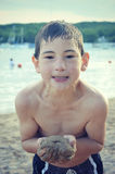 Muchacho que sostiene la arena en la playa Fotografía de archivo libre de regalías