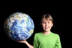 Muchacho que sostiene la bola de la tierra del mundo en su mano Fotos de archivo