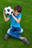 Muchacho que sostiene la bola del fútbol Imagen de archivo libre de regalías