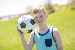Muchacho que sostiene la bola del pie en el parque Fotos de archivo