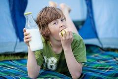 Muchacho que sostiene la botella de leche y que come Apple mientras que miente en la manta Imagenes de archivo