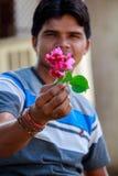 Muchacho que sostiene la flor roja en su mano Fotografía de archivo libre de regalías