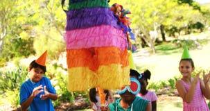 Muchacho que sostiene la marioneta multicolora mientras que celebra cumpleaños con los amigos almacen de video