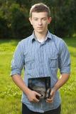 Muchacho que sostiene la tableta en césped de la hierba verde Imagenes de archivo