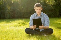 Muchacho que sostiene la tableta en césped de la hierba verde Foto de archivo
