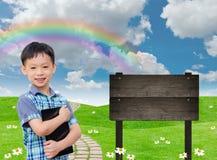 Muchacho que sostiene la tableta en campo verde Imagen de archivo