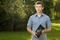 Muchacho que sostiene la tableta en hierba verde Fotografía de archivo