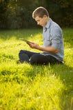 Muchacho que sostiene la tableta en hierba verde Fotos de archivo