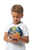 Muchacho que sostiene la tierra del planeta Imagen de archivo libre de regalías
