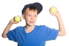 Muchacho que sostiene pelotas de tenis Foto de archivo libre de regalías