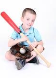 Muchacho que sostiene un bate de béisbol con la bola y el guante Foto de archivo libre de regalías