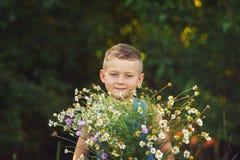 Muchacho que sostiene un ramo de flores salvajes Fotografía de archivo libre de regalías