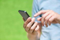 Muchacho que sostiene un teléfono y una pantalla táctil para el finger contra un gree Imagen de archivo libre de regalías
