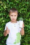 Muchacho que sostiene un vidrio de leche Foto de archivo