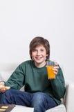 Muchacho que sostiene un zumo de naranja Imagen de archivo libre de regalías
