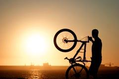 Muchacho que sostiene una bici de montaña contra el sol poniente Fotografía de archivo libre de regalías