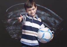 Muchacho que sostiene una bola Fotografía de archivo libre de regalías