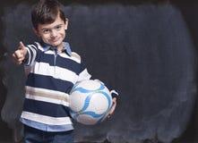 Muchacho que sostiene una bola Fotos de archivo