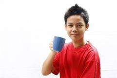 Muchacho que sostiene una taza Foto de archivo libre de regalías