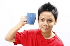 Muchacho que sostiene una taza Imagen de archivo libre de regalías