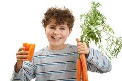 Muchacho que sostiene zanahorias frescas Imágenes de archivo libres de regalías