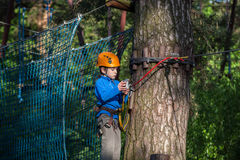 Muchacho que sube en el parque de la aventura, parque de la cuerda Fotos de archivo libres de regalías