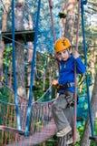 Muchacho que sube en el parque de la aventura, parque de la cuerda Imagen de archivo libre de regalías
