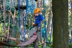 Muchacho que sube en el parque de la aventura, parque de la cuerda Fotografía de archivo libre de regalías