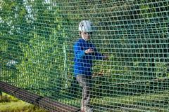 Muchacho que sube en el parque de la aventura, parque de la cuerda Imagenes de archivo