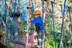 Muchacho que sube en el parque de la aventura, parque de la cuerda Imagen de archivo