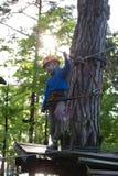 Muchacho que sube en parque de la aventura Foto de archivo libre de regalías