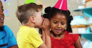 Muchacho que susurra a la muchacha mientras que se sienta con los amigos durante la fiesta de cumpleaños 4k almacen de video