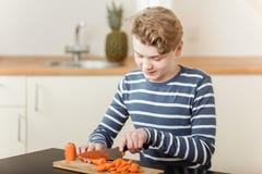 Muchacho que taja zanahorias en tabla de cortar en cocina Fotografía de archivo libre de regalías
