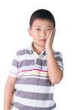 Muchacho que tiene un dolor de muelas que se sostiene la cara con su mano, aislada en el fondo blanco Imágenes de archivo libres de regalías
