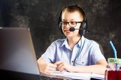 Muchacho que tiene una llamada video con las auriculares Foto de archivo libre de regalías