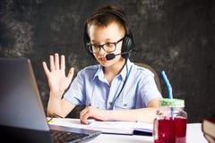 Muchacho que tiene una llamada video con las auriculares Fotos de archivo libres de regalías