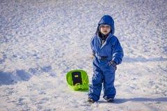 Muchacho que tira de un trineo en nieve Imágenes de archivo libres de regalías