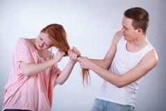 Muchacho que tira del pelo de la muchacha Foto de archivo libre de regalías