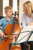 Muchacho que toca el violoncelo en la lección de música Imagen de archivo