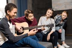 Muchacho que toca la guitarra acustic y que canta mientras que sus amigos que escuchan en casa Imagenes de archivo