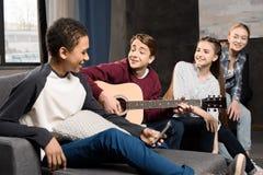 Muchacho que toca la guitarra acustic y que canta mientras que sus amigos que escuchan en casa Fotos de archivo