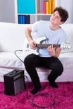 Muchacho que toca la guitarra eléctrica en su sitio Fotografía de archivo libre de regalías