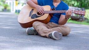muchacho que toca la guitarra en el parque de naturaleza al aire libre Fotografía de archivo