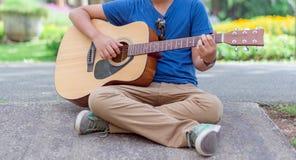 muchacho que toca la guitarra en el parque de naturaleza al aire libre Foto de archivo libre de regalías