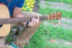 muchacho que toca la guitarra en el parque de naturaleza al aire libre Imagenes de archivo